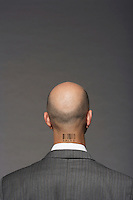 Bald headed businessman with barcode on his neck over gray background