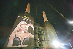 **CAPTION CORRECTION. INCORRECT DATES** © licensed to London News Pictures. London, UK 06/12/2011. Wonderbra fans participate in the launch of the Ultimate Plunge bra in a bungee jump in front of a gigantic projection of Wonderbra's new model Adriana Cernanova at London's landmark Battersea Power Station early this morning (06/12/2011). Photo credit: Tolga Akmen/LNP