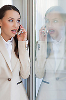 Shocked businesswoman using cell phone in office