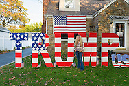 "Bellmore, New York, USA. November 2, 2016. EILEEN FUSCALDO, a Donald Trump Supporter, stands in front of TRUMP display, one of many in her front yard for the Republican presidential candidate, D. J. Trump, and against Democratic one, H. R. Clinton.  On her front door is a life-size cardboard Trump holding ""The Silent Majority Stands with Trump"" sign."