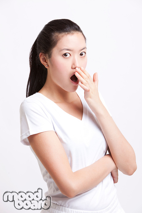 Portrait of shocked young woman with hand over mouth against white background