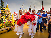 30 OCTOBER 2014 - BANGKOK, THAILAND: Brahmin priests carry the red cloth that will  around the chedi at Wat Saket during the parade marking the start of the temple's annual fair. Wat Saket is on a man-made hill in the historic section of Bangkok. The temple has golden spire that is 260 feet high which was the highest point in Bangkok for more than 100 years. The temple construction began in the 1800s in the reign of King Rama III and was completed in the reign of King Rama IV. The annual temple fair is held on the 12th lunar month, for nine days around the November full moon. During the fair a red cloth (reminiscent of a monk's robe) is placed around the Golden Mount while the temple grounds hosts Thai traditional theatre, food stalls and traditional shows.   PHOTO BY JACK KURTZ