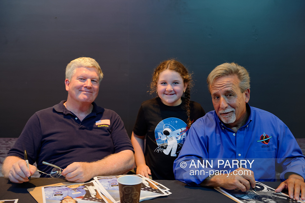 Garden City, New York, U.S. July 20, 2019. L-R, NASA Space Shuttle astronaut  BILL SHEPHERD, ADRIANA IACONO, 6, of Franklin Square, and Space Shuttle astronaut CHARLIE CAMARDA, are at the astronaut autographing table, at the Moon Fest Apollo at 50 Countdown Celebration at Cradle of Aviation Museum in Long Island, during the time Apollo 11 Lunar Module, The Eagle, landed on the Moon 50 years ago.