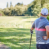 A photograph of a golfer waiting his turn to tee off as he surveys the fairway on a sunny day in England