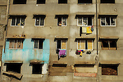 An empty apartment block has become the home of squatters, The resettlement projects are not as successful as expected, partly due the financial crisis.
