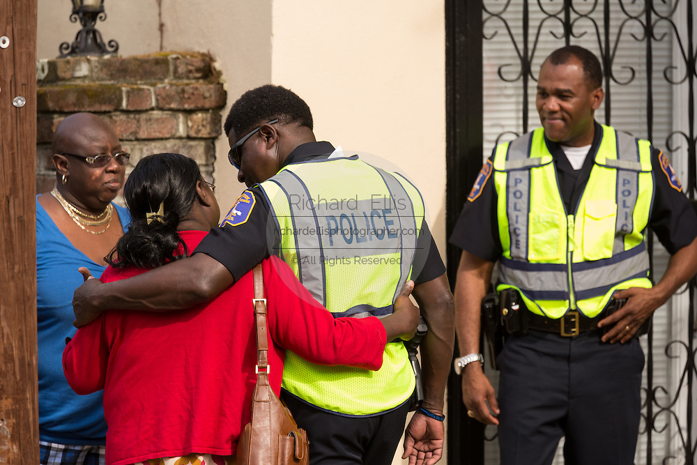 Charleston Police comfort mourners gathered outside the Fieldings Funeral home where the viewing for Walter Scott was held April 10, 2015 in Charleston, South Carolina. Scott was shot multiple times in the back and died on the scene after running from police in North Charleston.