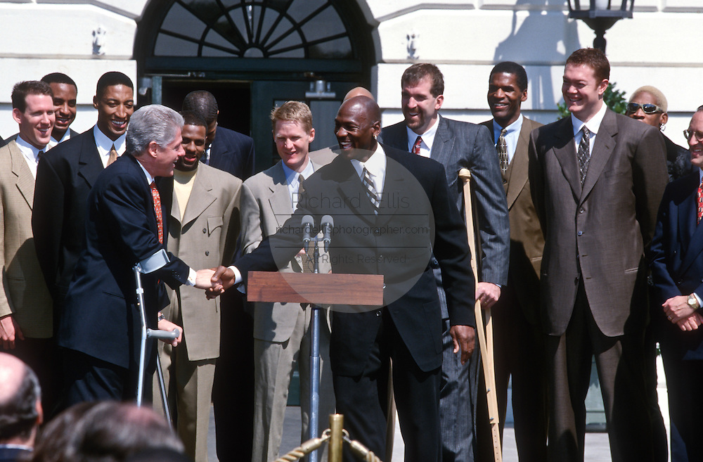 President Bill Clinton shows off his Chicago Bulls jacket gifted him by President Bill Clinton shakes hands with Chicago Bulls star Michael Jordan during an event on the South Lawn of the White House April 3, 1997. The event honored the NBA Champion Chicago Bulls.