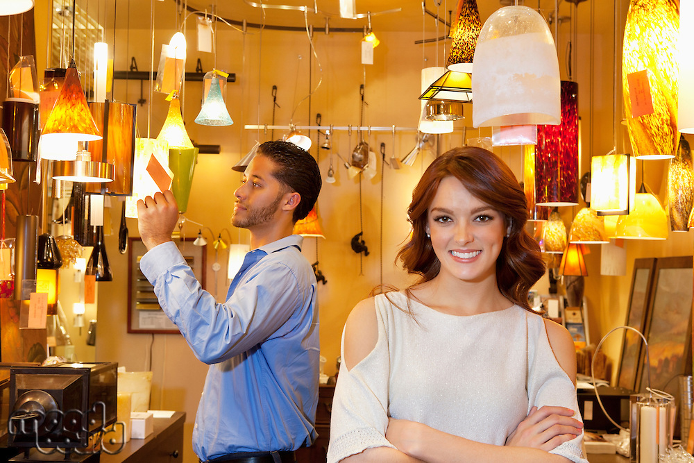 Portrait of young woman with arms crossed while man looking at price tag in background in lights store