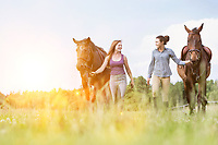 Portrait of women walking while talking with their horses in ranch