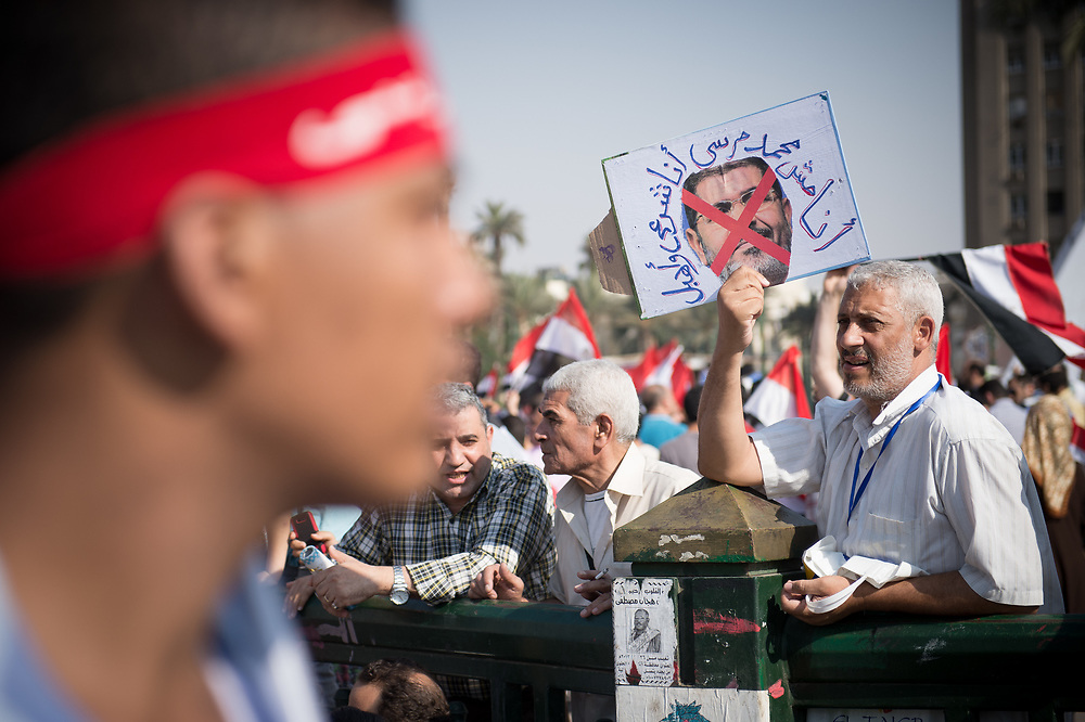 A protester holds a crossedout picture of President Morsi during an anti-Morsi rally on Tahrir Square in Cairo, Egypt, July 3, 2013