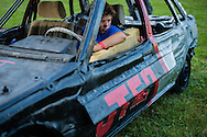 """Deagan Foster, 13, waits in his demolition derby car as his father completes final tightening of bolts to make the car  race ready, Thursday, July 27, at the Summitt County Fairgrounds in Tallmage, Ohio. Deagan, his sister Lilly, and father John, make up what he desicribes as, the """"FFDT"""", or """"Foster family derby team,"""" started by John's father, and passed down over generations. The car Deagan drives is graced with the word 'Pop', in homage to the family's derby patriarch."""