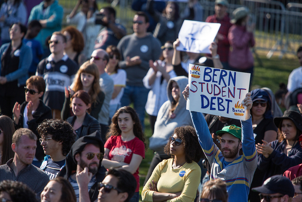 "Brooklyn, NY - 17 April 2016. A man holds a sign reading ""Bern studet debt."" Vermont Senator Bernie Sanders, who is running as a Democrat in the U.S. Presidential primary elections, held a campaign ""get out the  vote"" rally in Brooklyn's Prospect Park."