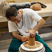 Man using wheel to throw pottery in a ceramics class.