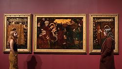 """© Licensed to London News Pictures. 22/10/2018. LONDON, UK. Staff members view """"The Annunciation and the Adoration of the Magi"""", 1861, by Edward Burne-Jones.  Preview of the largest Edward Burne-Jones retrospective to be held in a generation at Tate Britain.  Burne-Jones was a pioneer of the symbolist movement and the only Pre-Raphaelite to achieve world-wide recognition in his lifetime.  The exhibition runs 24 October to 24 February 2019.  Photo credit: Stephen Chung/LNP"""