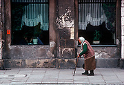 An elderly 1990s Polish lady struggles along a street and past a cafe whose walls are crumbling - the heritage of polluted communist decades, on 15th July 1990, in Krakow, Poland. (Photo by Richard Baker / In Pictures via Getty Images)