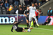 Martin Olson (3) of Swansea City skips over a tackle by Liam Kelly (38) of Reading during the EFL Sky Bet Championship match between Swansea City and Reading at the Liberty Stadium, Swansea, Wales on 27 October 2018.