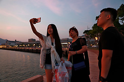 Transgender couple Chen Zhichao (R), her mother (C) and partner  Yang Jieli (L) takes a selfie during a stopover of a cruise organised by the Parents and Friends of Lesbians and Gays (PFLAG) China organisation at Sasebo, Nagasaki, Japan, 16 June 2017. About 800 members of the Chinese LGBT (lesbian, gay, bisexual and transgender) community and their parents spent four days on a cruise trip organised by Parents and Friends of Lesbians and Gays (PFLAG) China, a grassroots non-government organisation, celebrating the 10th anniversary of the organisation. It aims to promote coexistence among homosexuals and their families.