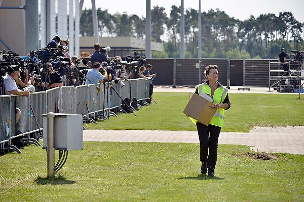 Nederland, Eindhoven,23-7-2014Voordat de twee vliegtuigen met lijkkisten landen maakt een vrouw nog even het grasveld schoon. De verzamelde internationale pers staat achter het hek..Na aankomst van de twee transportvliegtuigen  op de militaire vliegbasis worden de slachtoffers van de vliegramp boven de Oekraine een voor een naar rouwwagens, lijkwagens, gebracht en vervolgens in colonne naar Hilversum gebracht.The arrival of corpses, remains, of the victims of flight MH17 which was shot down over Ukraine.FOTO: FLIP FRANSSEN/ HOLLANDSE HOOGTE
