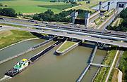 Nederland, Gelderland, Tiel, 28-06-2006; Prins Bernhardsluis in het Amsterdam-Rijn Kanaal; schutsluis tussen Kanaal en rivier de Waal; duwbak met erts (kolen) vaart sluiskom binnen; de sluis wordt gekruist door (van boven naar beneden) autosnelweg A15, Betuweroute, lokale verbindingsweg; scheepvaart, binnenvaart, waterstaat,  verkeer en vervoerbouw, transport, infrastructuur, infrabundel, mobiliteit, planologie, Betuwlijn; zie ook andere (lucht)foto's van deze lokatie, deel van de serie Panorama Nederland luchtfoto (toeslag aerial photo (additional fee required .foto Siebe Swart / photo Siebe Swart