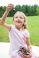 Happy young girl holding bowl full of bing cherries in park