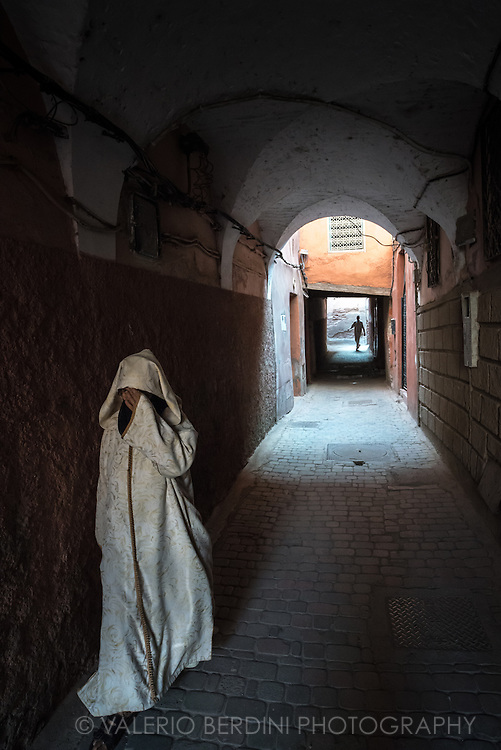 A woman in a tunic walks in an alley of Marrakech's medina