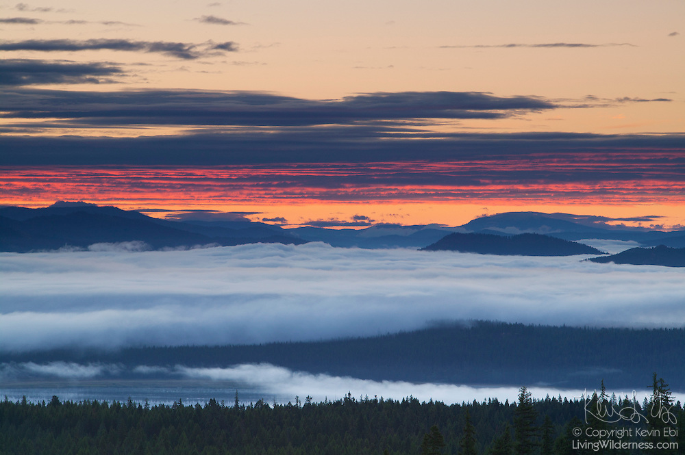 Fog rises from the Pend Oreille River as the sunrise reddens the clouds above mountains in the Colville National Forest near Newport in Washington state.