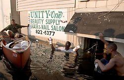 05 Sept  2005. New Orleans, Louisiana. Post hurricane Katrina.<br /> L/R Jonas Smith and his father John and brother John swim through the murky water in Uptown New Orleans as the family attempt to rescue their business.<br /> Photo; ©Charlie Varley/varleypix.com