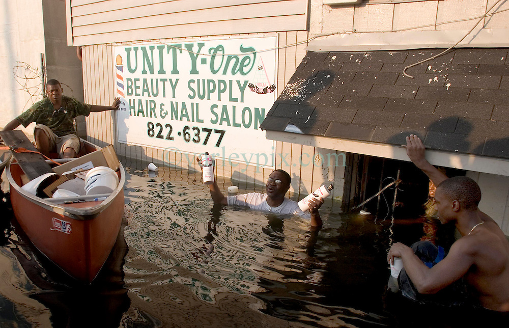 05 Sept  2005. New Orleans, Louisiana. Post hurricane Katrina.<br /> L/R Jonas Smith and his father John and brother John swim through the murky water in Uptown New Orleans as the family attempt to rescue their business.<br /> Photo; &copy;Charlie Varley/varleypix.com
