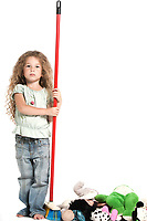 caucasian little girl sweeping toys serious isolated studio on white background