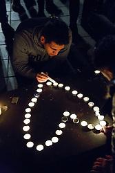 © Licensed to London News Pictures. 14/11/2015. Paris, France. Mourners leaving candles and flowers at Place de la République in Paris, France following the Paris terror attacks on Saturday, 14 November 2015. Photo credit: Tolga Akmen/LNP
