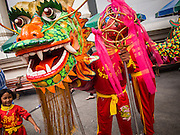 17 AUGUST 2013 - BANGKOK, THAILAND:    Members of a Dragon dance troupe relax between performances at Erawan Shrine in Bangkok. The Chinese Dragon Dance began during the Han Dynasty which lasted from 206 BC to 24 AD. In those ancient days it was performed by the people of China specifically to please their ancestors and to insure sufficient rain for a plentiful crop. In this way they hoped to protect against hunger and sickness. Over time the Dragon Dance became a central feature in Chinese celebrations with different colors symbolizing different characteristics or desired features; red for excitement, green for a good harvest, yellow for a solemn empire and gold or silver for prosperity. The Dragon Dance is a well-choreographed event whose difficulty is dependent upon the performers' skill. The length of the dragon indicates just how much luck it will bring in the coming year, but a longer dragon requires more performers with great skill as an error by one can ruin the entire performance. The dragon is typically between 82 and 229 feet long. The head along can weigh as much as 31 pounds. Both strength and skill are both required in performing the Chinese Dragon Dance.        PHOTO BY JACK KURTZ