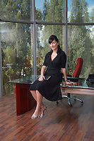 Young business woman sitting on desk in office portrait
