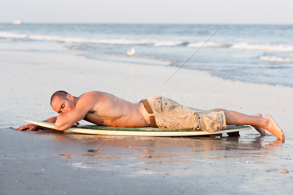 Man in shorts relaxing on his surfboard at the beach