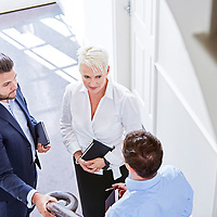 A photograph of three colleagues having an impromptu meeting in a hallway at work