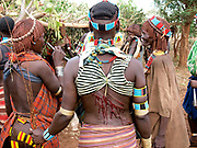 Whipping of young women in Ethiopian Tribal ceremony<br /> <br /> To the south of Addis Ababa, capital of Ethiopia, lies the tribal animist area. It stretches from Addis all the way to Lake Turkana, formerly known during colonial times as Lake Rudolph, which borders Kenya.<br /> <br /> The italian historian Carlo Conti Rossini has described this part of Ethiopia to be a Museum of People's as there are at least eight major tribal groups living here -  numbering around 200,000,<br /> who until recently were largely untouched by outside influences. But change is on the way, not least the impact of global phone technology  - and the development of the country's mineral resources by the Chinese.<br /> <br /> The annual flooding of the Omo River has been the life-support for the tribal people of this region.  For centuries the powerful flow and huge rise and fall of the river have provided up to three harvests a year for the indigenous people's staple crop - the highly nutritious SORGHUM<br /> <br /> But in 2006 President Meles Zenawi of Ethiopia commissioned the construction of the tallest hydro-electric dam in Africa.  The project was never put to tender, the tribal groups never consulted,<br /> and conservation groups today believe that the dam will destroy an already fragile environment as well as the livelihoods of the tribes, which are closely linked to the river and its annual flood.<br /> <br /> One of the most spectacular ceremonies in the Lower Omo Valley is the UKULI BULA ceremony of the Hamar tribal group; it's effectively a Rite-of-Passage from boy to manhood. And marriage.<br /> To reach manhood, Hamar boys must undergo two rituals: circumcision and a leap over the bulls. This determines whether the young Hamar male is ready to make the social jump from youth to adulthood. <br /> After a successful bull-jump - always naked - the Hamar boy, now a Maz - a mature member of the society - may get married.<br /> At every ceremony around two hundred members of the Hamar (also spelt Hamer) participate in this life-changing event. <br /> <br /> Hamar women ar