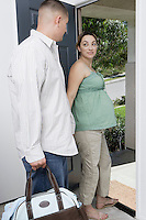 Expectant couple exiting house