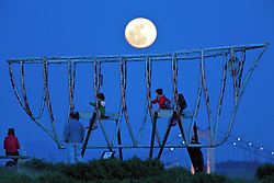 "People watch from the Mare Island ""Spirit Ship"" as a Perigee Moon rises over the Alfred Zampa Memorial Bridge spanning the Carquinez Strait in Vallejo, California.  The ""Supermoon"" appears 14 percent larger and 30 percent brighter as it makes it's closest approach to the earth this year."