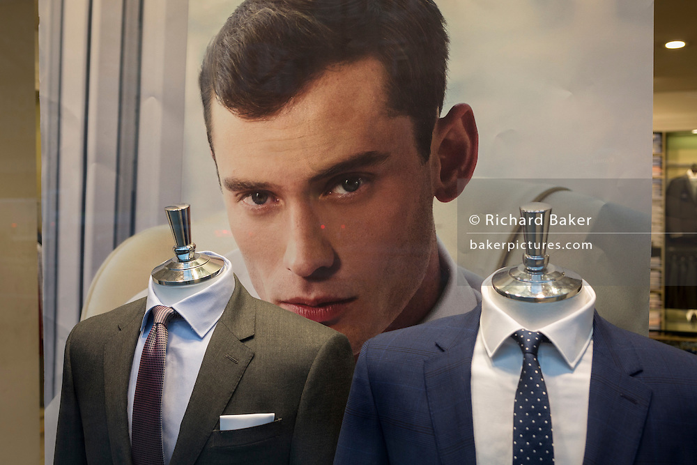 Millennial suits fashion and a model's face looking out fron the window of a meanswear retailer, on 9th February 2017, in the City of London, England.