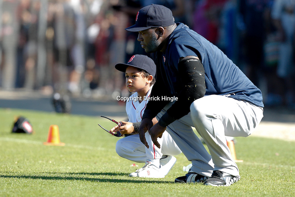February 19, 2011; Fort Myers, FL, USA; Boston Red Sox first baseman David Ortiz and son D'Angelo Ortiz stretch during spring training at the Player Development Complex.  Mandatory Credit: Derick E. Hingle