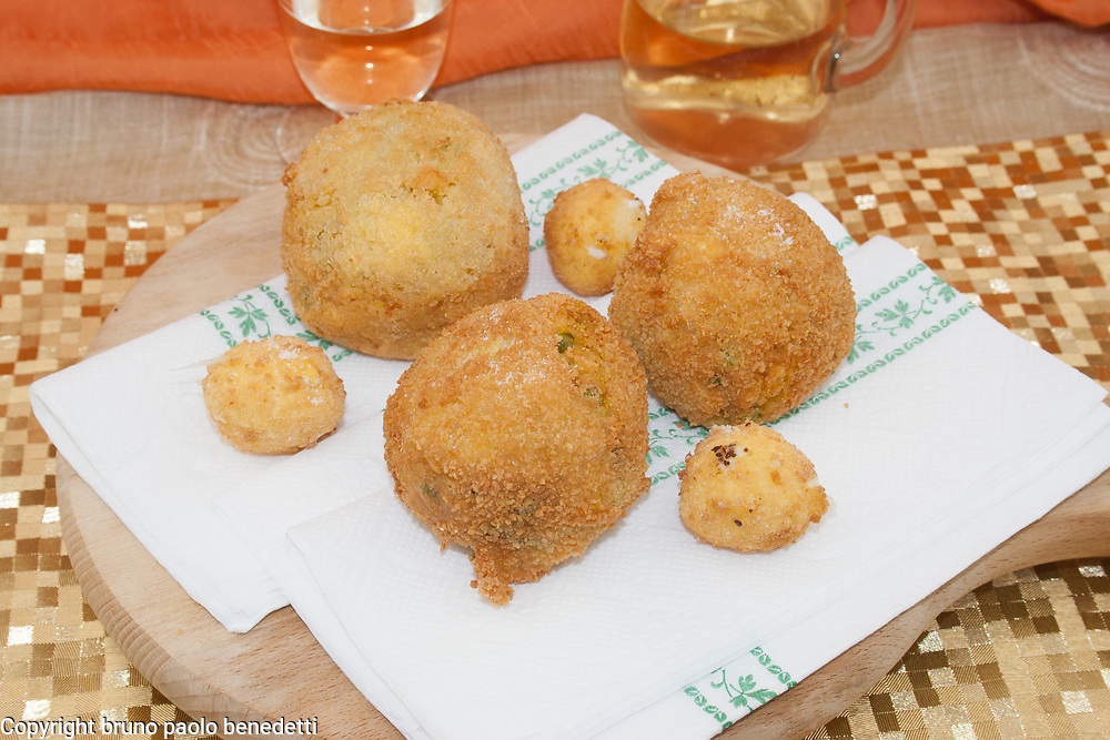 Sicilian arancini, fried rice balls side view from above on wooden chopping board and ehite wine and orange veil on background, italian food of Sicily
