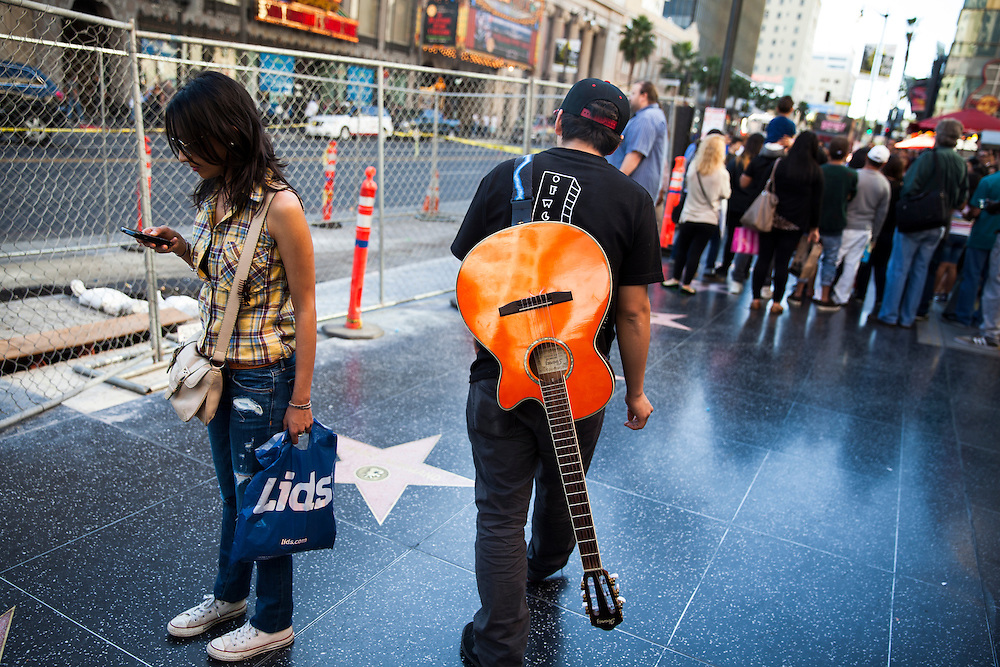A man walks with his guitar down the famed Hollywood Boulevard.