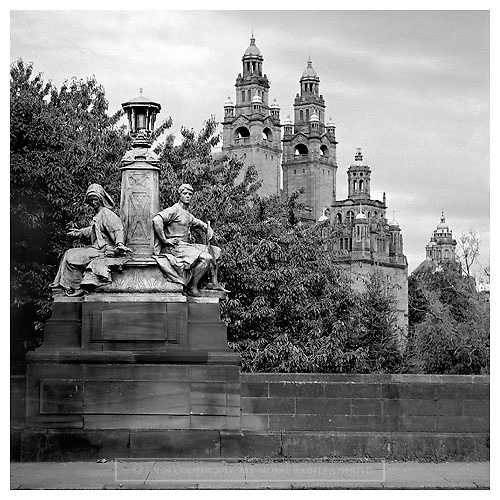 Black and white photograph of sculptural street lamp on Kelvin Way and Kelvingrove Art Gallery & Museum in Glasgow.