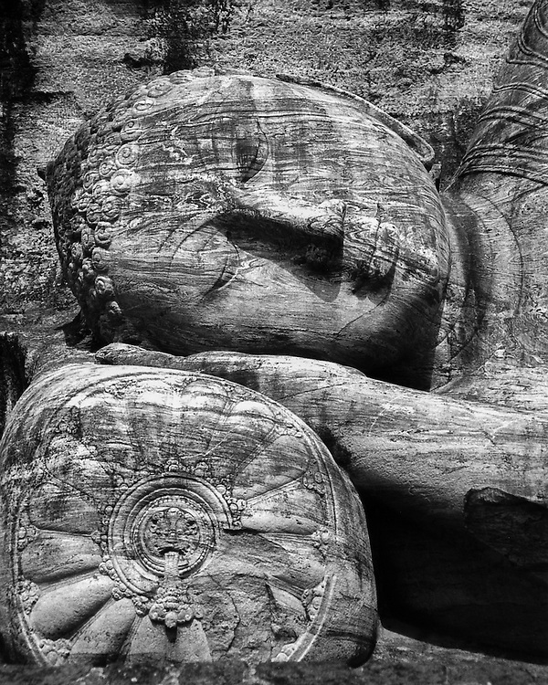 Giant reclining buddha statue carved out of stone in Polonnaruwa, Sri Lanka