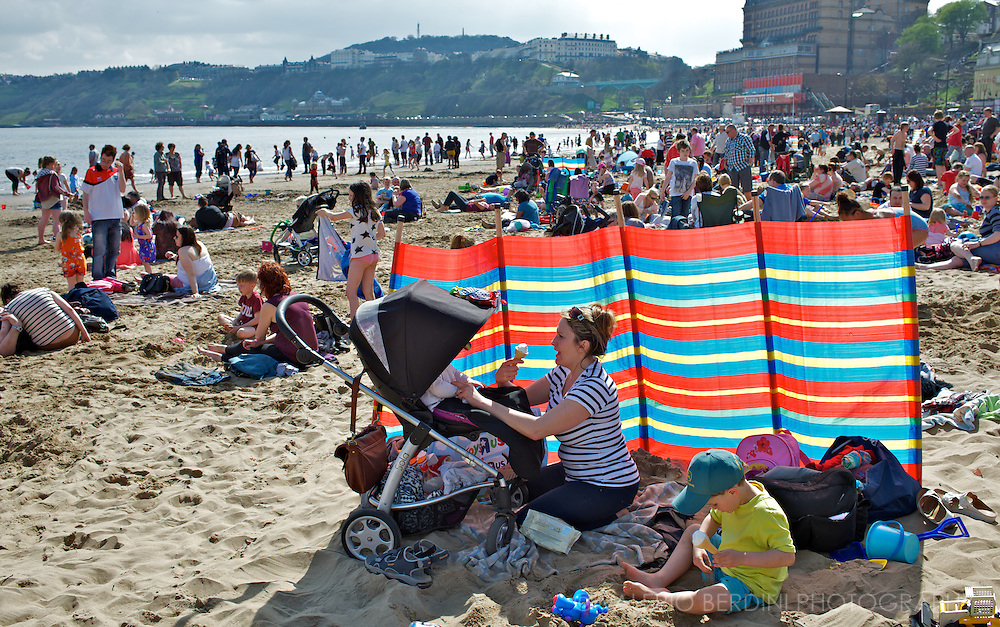 Mother in the shades of a sunny day eats an ice-cream while looking after her two children in the busy beach of Scarborough in England. A pairwise selection to stimulate a reflection about the English seaside.
