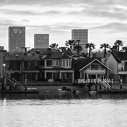 Newport Beach skyine sunrise black and white panorama photo with Balboa Island homes, Newport Harbor, and Fashion Island office buildings. Newport Beach is an affluent coastal city in Orange County Southern California in the United States of America. Panorama photo ratio is 1:3. Copyright ⓒ 2017 Paul Velgos with All Rights Reserved.