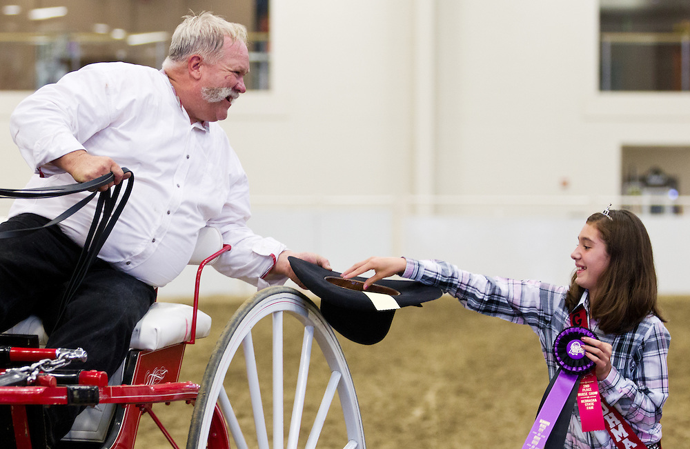 Michael Gustafson of Blanco, N.M., accepts a ribbon from the Draft Horse Queen, Meghan Phaby of Cozad, Neb., during the Draft Horse Hitch show Friday evening in the Five Points Bank Arena at the Nebraska State Fair in Grand Island. (Independent/Matt Dixon)