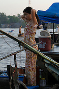 Mekong Delta. Early morning at Cai Rang Floating Market on Can Tho River. Young lady doing her hair.