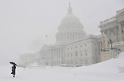 A person stands near the U.S. Capitol as snow falls in Washington, D.C.