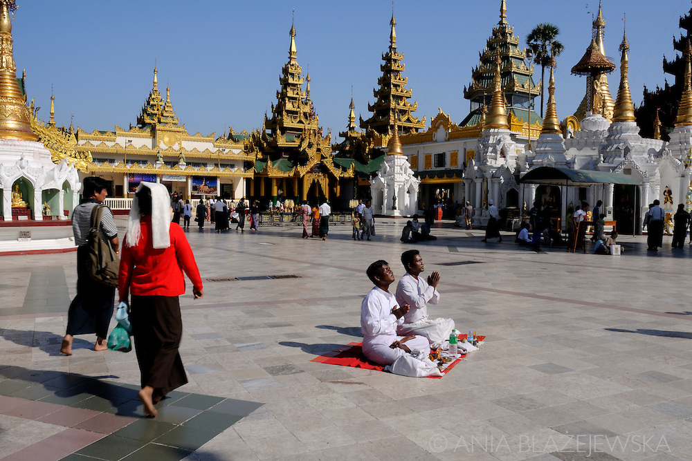 Myanmar/Burma, Yangon. People praying in the Shwedagon Paya, the most famous buddhist temples and travel destinations in Yangon.