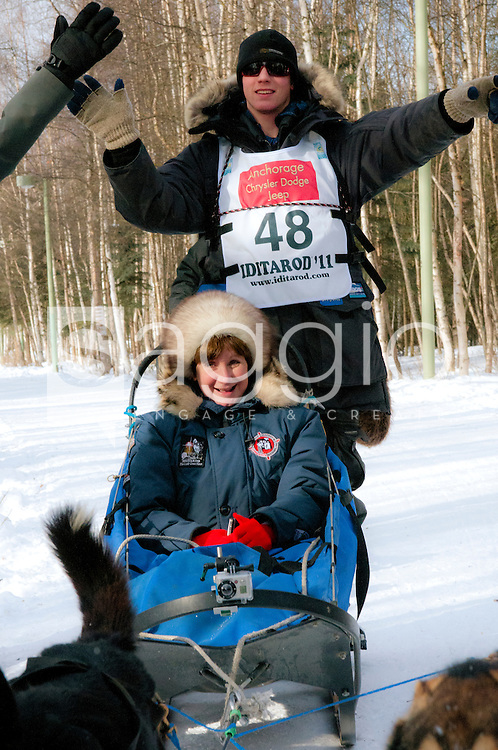 Musher Cain Carter and Iditarider Janet Tremer give high-fives as they pass through a crowd of fans along the Chester Creek Trail during the 2011 Iditarod Ceremonial Start.